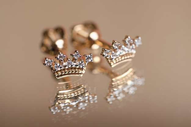 Children's earrings in the form of a golden crown on the mirror.