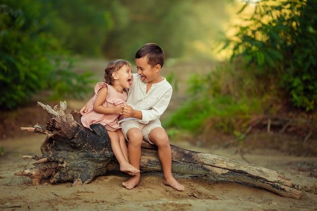 아이들의 감정. 쾌활한 정서적 아이들 형제와 자매는 모래에 강가에 의해 오래된 마른 나무에 앉아있다. 그들은 열렬히 웃었다