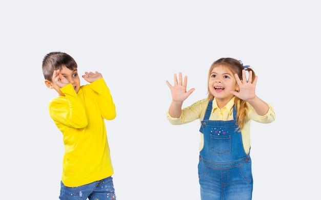 子供の感情。女の子は別の顔をして友達を怖がらせます。白い背景の上の写真。