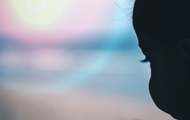 Children's face silhouette, which is playing on the beach, is a blurry background.