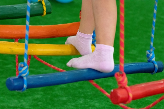 Детские ножки на детской площадке с качающимся мостиком.