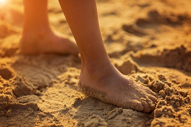 Children's feet on the beach in the sand close-up