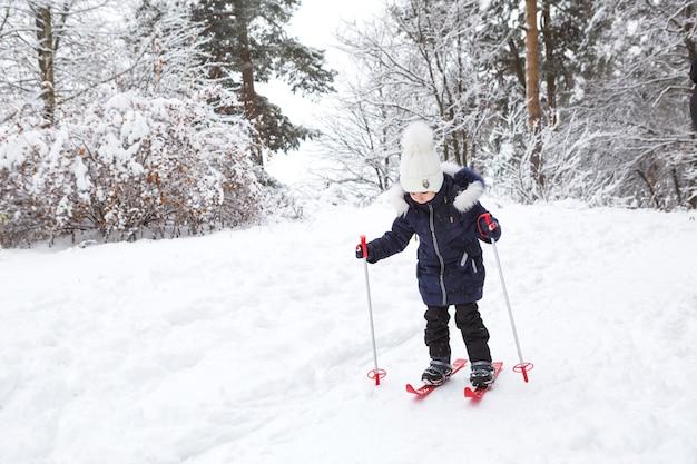 スティック付きの赤いプラスチックスキーの子供の足は、スライドから雪を通り抜けます-ウィンタースポーツ
