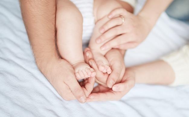 부모의 손에있는 어린이 발. 아버지의 개념적 이미지.