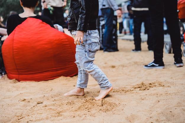 子供の足は砂の上にある。裸足