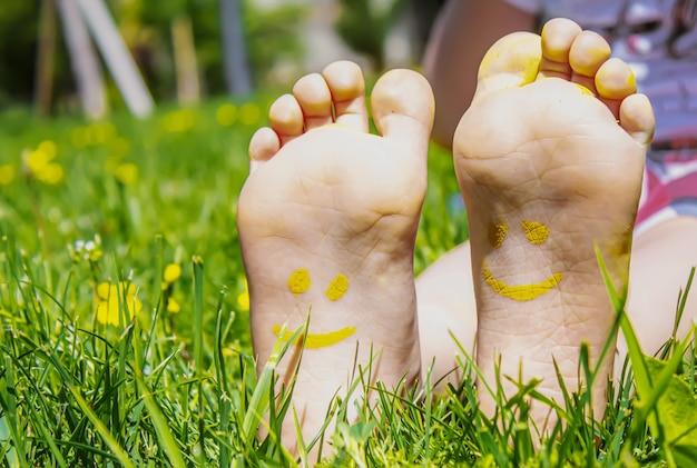 絵の具の模様が描かれた子供の足は、緑の芝生の上で微笑んでいます。セレクティブフォーカス。自然。