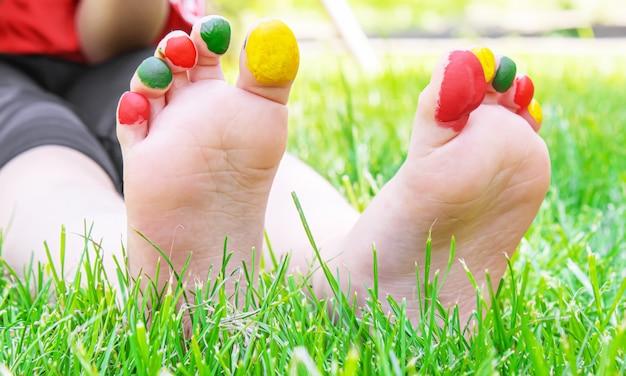 Детские ножки с рисунком красок улыбаются на зеленой траве. выборочный фокус. природа.