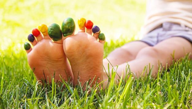 絵の具の模様が描かれた子供の足は、緑の芝生に微笑んでいます。セレクティブフォーカス。自然。