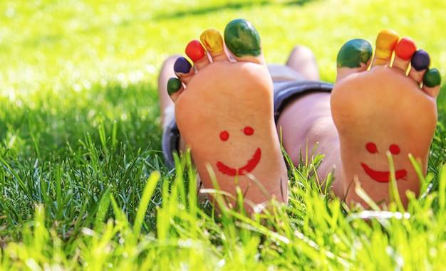 絵の具の模様が描かれた子供の足は、緑の芝生に微笑んでいます。セレクティブフォーカス。