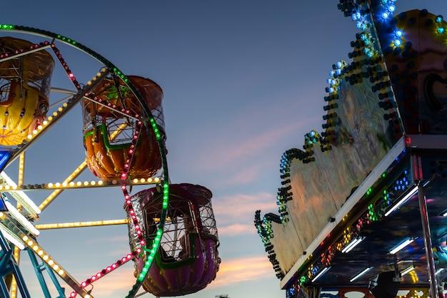 Детское колесо обозрения, украшенное множеством огней и рисунков, в сумерках на рождественской ярмарке.