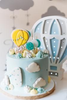 子供の最初の誕生日ケーキ、雲、メレンゲ、風船と青いケーキ