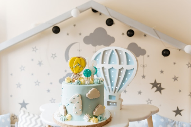 Children's first birthday cake, blue cake with clouds, meringue and balloons in the children's room