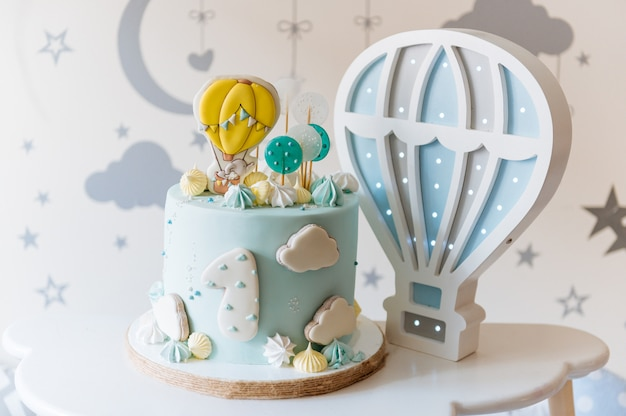 Children's first birthday cake, blue cake with clouds, meringue and balloons