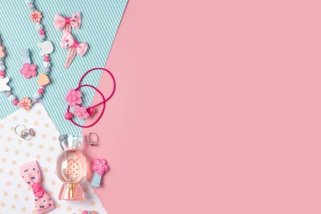 子供のフラットレイ。ピンクのキャンディー、子供用ジュエリー、ヘアアクセサリーの形の香水