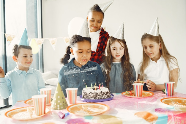 Children's funny birthday party in decorated room. happy kids with cake and ballons.