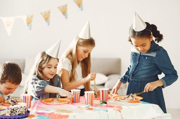 장식 된 방에서 아이들의 재미있는 생일 파티. 케이크와 풍선을 가진 행복한 아이들.