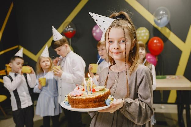 Детский веселый день рождения в украшенной комнате. счастливые дети с тортом и баллонами.