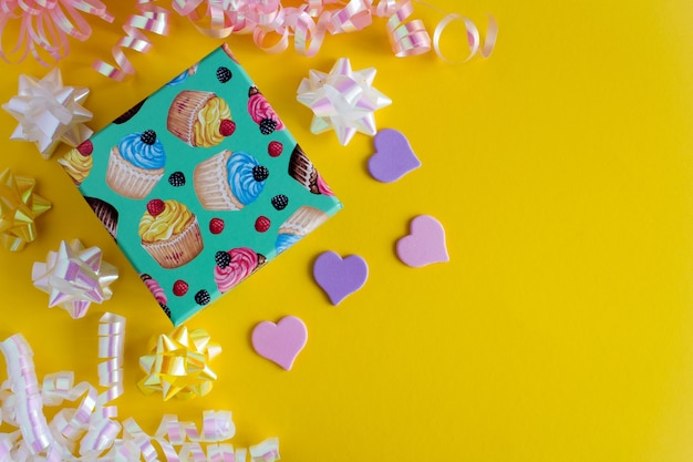 Children's gift with colorful confetti on the yellow background