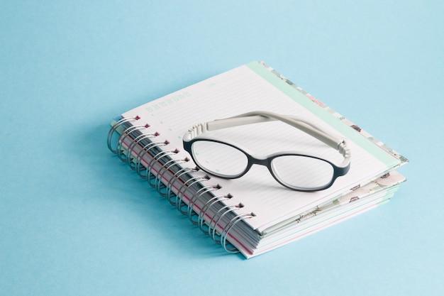 ノートブック、青い背景の上の子供用メガネ
