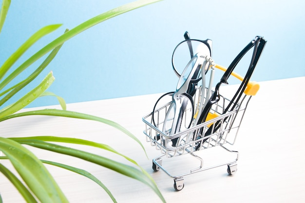 Children's glasses and two pairs of black glasses for adults are in a small shopping trolley on a blue surface