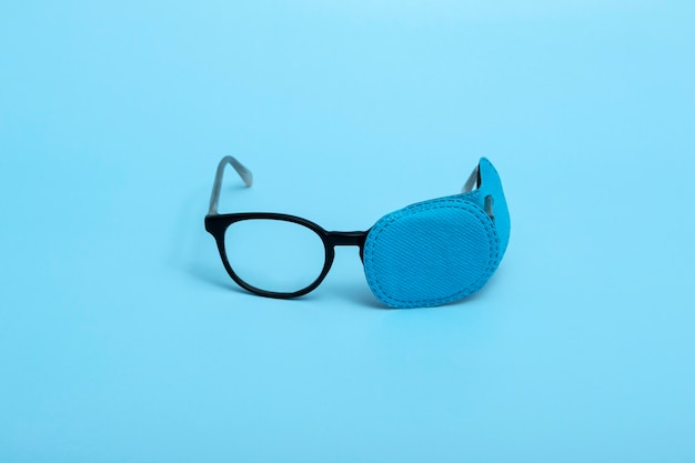 Children's glasses with occluder on a colored background. lazy eye. amblyopia