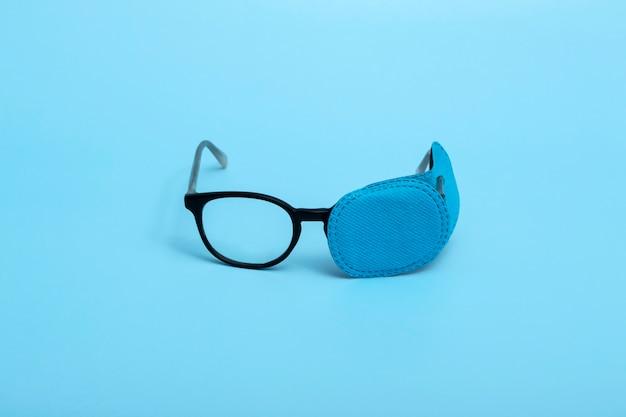 色付きの背景にオクルーダー付きの子供用メガネ。怠惰な目。弱視