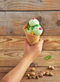 Children's hand holding a pistachio ice cream cone