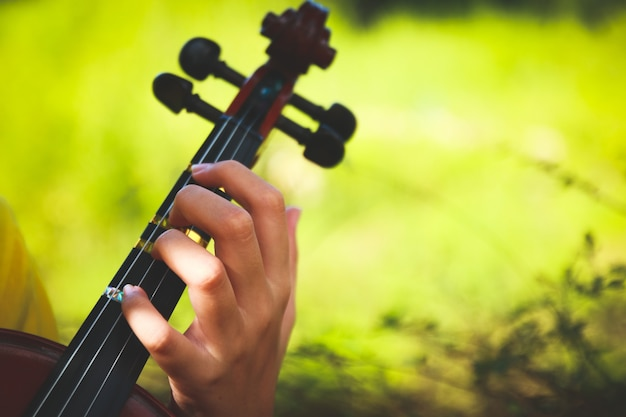 Children's hand holding violin string playing in the garden.