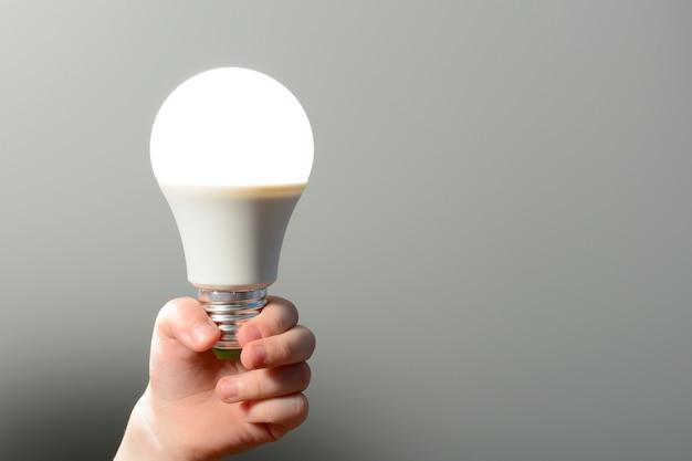 어린이 손에 빛나는 led 전구가 있습니다.