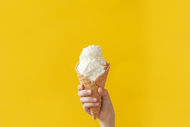 Children's hand holds delicious vanilla ice cream cone on a bright yellowwith copy space