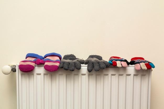 Children's hand knitted woolen gloves drying on heat