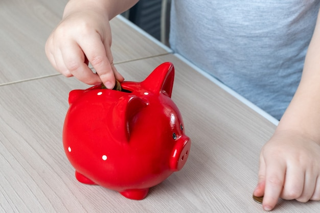 Children's hand puts a coin in a red piggy bank on a wooden surface, top view, copy space. money saving concept