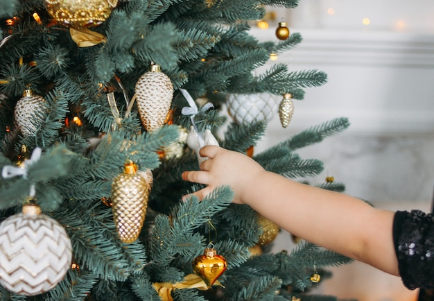 Children's hand reaches for toys on christmas tree