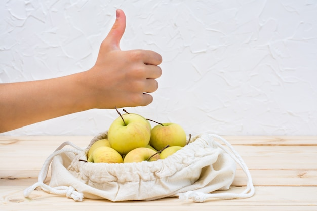 Children's hand shows ok over a canvas bag on ties with apples on a natural wooden . zero waste