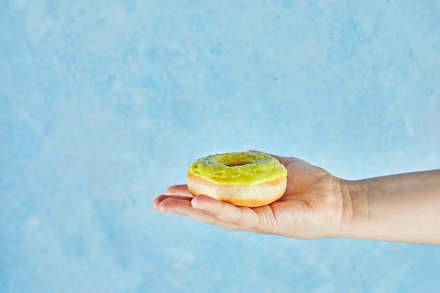 파란색 바탕에 도넛과 어린이 손.