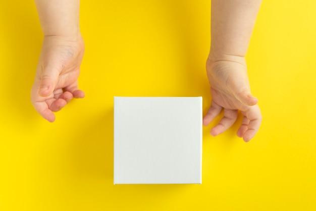 子供の手と黄色の背景、上面図の白い段ボール箱。スペースをコピーします。モックアップ。