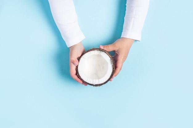 子供の手は青い背景にココナッツの半分を持っています。