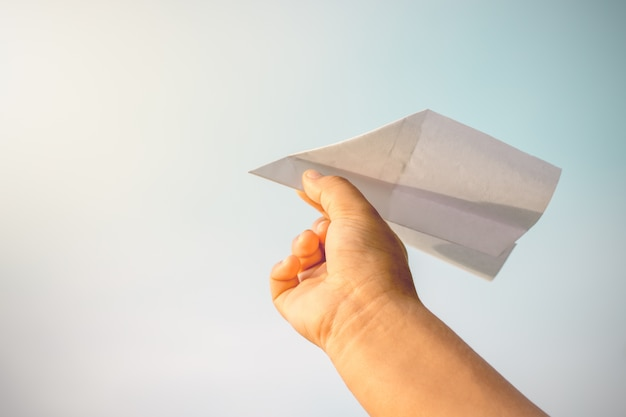 아이들의 손이 종이 비행기를 집어 들고 있습니다.