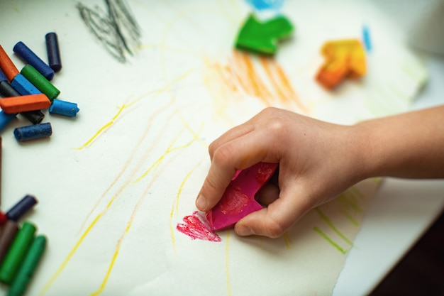 Children's hands draw with homemade wax pencils from fragments of old crayons