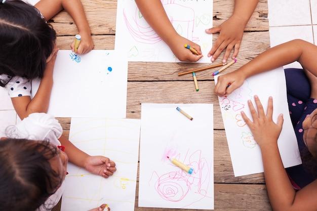 어린이 손 나무 테이블에 색연필으로 그리기