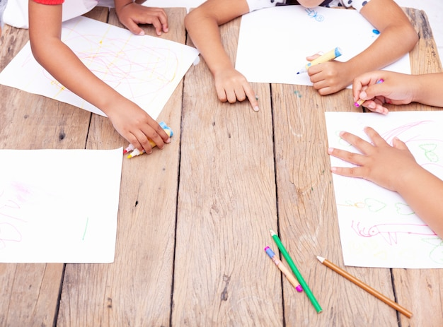 Children's hands drawing with colored pencils on wooden table