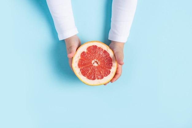 子供の手は青い背景にカット半分のグレープフルーツを保持します