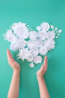 子供の手は、ネオミントの背景に花の心を持っています。愛の概念