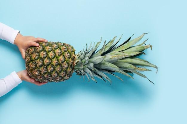 子供の手は青い背景にパイナップル全体を保持します