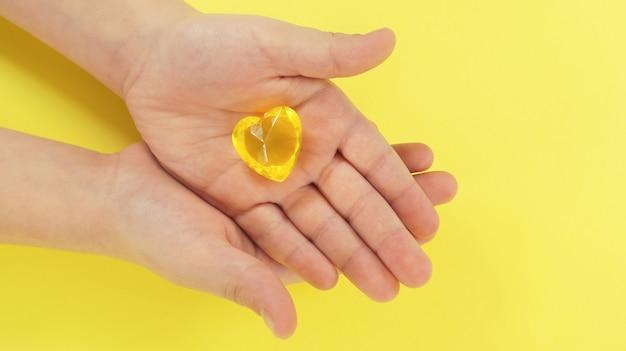 子供の手は黄色の背景に黄色のガラスのハートを保持します。希望、愛、アイデア、寄付、慈善、優しさ、喜び