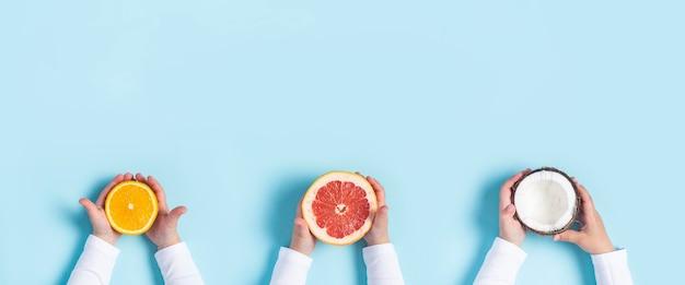 子供の手は青い背景にオレンジ、グレープフルーツ、ココナッツを保持します。