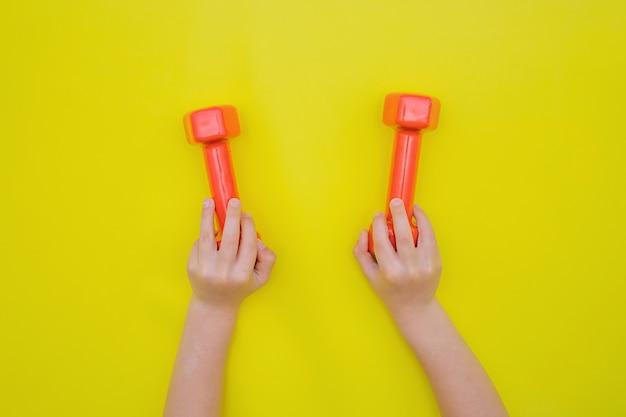子供の手は赤いダンベルを持っています。スポーツと健康的なライフスタイルの概念。
