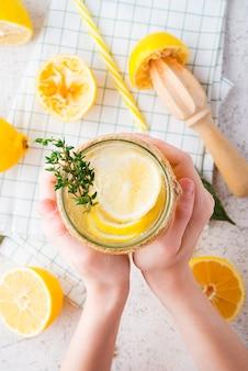 Детские руки держат банку домашнего лимонада, детокс-воду с лимоном, вид сверху