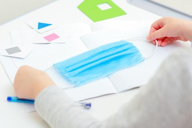 自宅の机の上の学校のノートの上に医療用保護マスクを持っている子供の手。検疫研究の概念。