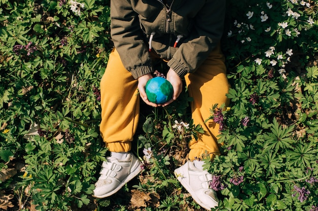 녹색 봄 배경 지구를 들고 어린이 손.